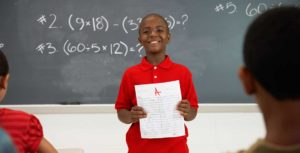 African American boy holding A+ paper in front of class